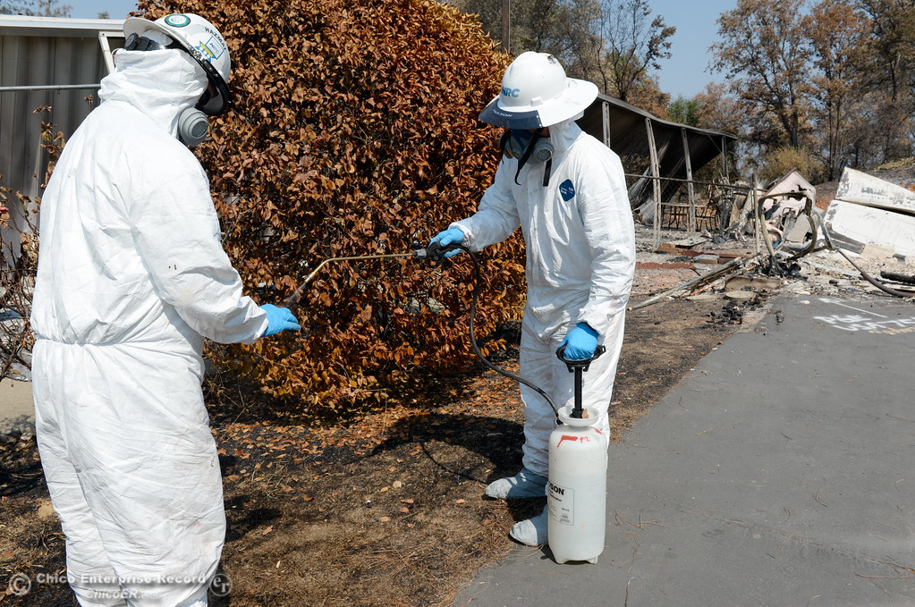 . NRC Employees spray each other down with water before removing their personal protection equipment as Department of Toxic Substances Control and representatives from NRC search the ashes of a home burned during the Wall Fire off of Old Olive Hwy. for toxic substances and hazardous waste Wed. Aug. 2, 2017. (Bill Husa -- Enterprise-Record)