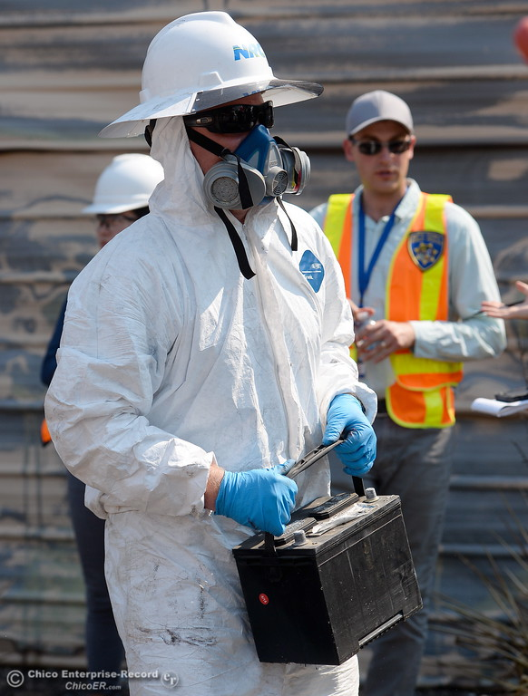 . An NRC Employee carries out a battery as Department of Toxic Substances Control and representatives from NRC search the ashes of a home burned during the Wall Fire off of Old Olive Hwy. for toxic substances and hazardous waste Wed. Aug. 2, 2017. (Bill Husa -- Enterprise-Record)