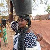 Photo: NRC/Ingrid Prestetun <br /> <br /> Hady Traorè (Women with black head scarf and a baby) lives close to the water post. Since she does not have so long to walk, she can fill up her 15 liter bucket and easily carry it home on the head. <br /> <br /> There are living approx. 25.000 people in town of Bargondaga. Even though the town is situated along the rivers Bani and Niger, clean water is a problem in the town. Before the families had to get water from the river which was their only source. Due to pollution, many people got skin diseases and suffered a lot.<br /> <br /> NRC drilled for fresh water and built this water post. This is the only source of clean fresh water for 12.000 persons in the village. The water post is an important and popular place in the town. The activity at the water hole is overlooked by one member of town council, Osmane Konta.