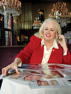 "Professional Matchmaker Dianne Bennett looks over photos of her ""stable"" of women while sitting at La Boheme in West Hollywood, February 08, 2006. Photo by Tom Sorensen"