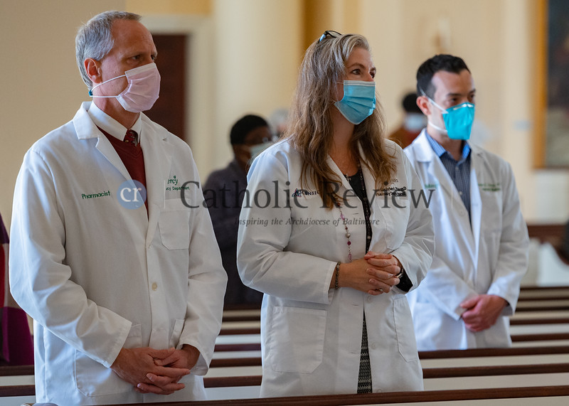 Husband and wife pharmacists from left, John and Christine Sybert, with Mercy Medical Center and St. Agnes Hospital respectively, and Mercy Medical Center internal medicine physician Dr. Ralph Lebron, stand during the blessing of health care professionals by Archbishop William E. Lori at the conclusion of the annual White Mass Oct. 18 at the Basilica of the National Shrine of the Assumption of the Blessed Virgin Mary in Baltimore. (Kevin J. Parks/CR Staff)
