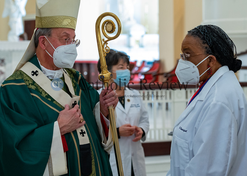 Archbishop William E. Lori talks with Catholic Medical Association past president and parishioner of the Basilica of the National Shrine of the Assumption of the Blessed Virgin Mary in Baltimore, Dr. Marie-Alberte Boursiquot, following the annual White Mass Oct. 18.(Kevin J. Parks/CR Staff)