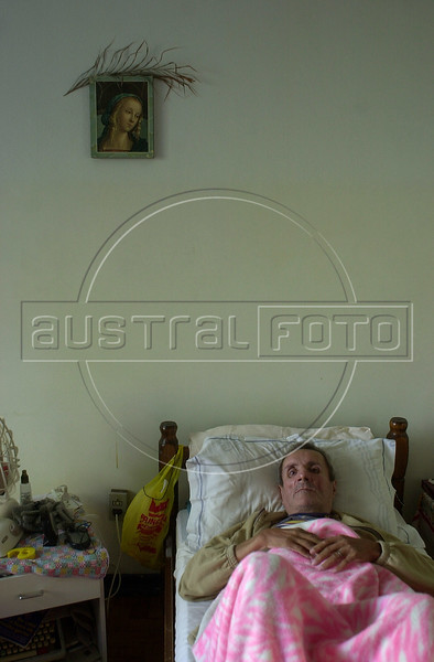 """HIV positive Alfredo Areal rests at a Catholic Church support house for HIV and AIDS patients in Rio de Janeiro, Brazil, in this photo taken November 9, 2000. Areal is one of 14 men and nine orphan children living at the house, founded six years ago to help paitients carry on with their lives in spite of a terminal disease. A top U.N. official said an AIDS epidemic is ravaging Latin America this week at an AIDS conference this week in Rio. But Brazil, the largest Catholic country in the world with more than 70 percent of its 165 million people claiming to Catholic, drew praise for its handling of the disease during the conference. The Federal government supplies a free """"cocktail"""" of anti-AIDS drugs to 90,000 victims, and AIDS deaths in Brazil were cut in half between 1996 and 1999. Some 540,000 Brazilians, or 0.57 percent of the population are registered as HIV-positive.(Australfoto/Douglas Engle)"""