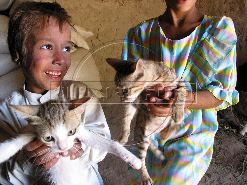 Sari Zegum, 10 and sister Noora, also 10, play with cats in their home in the countryside south of Baghdad. His family does not have much money, but with plentiful crops and livestock, he leads a rich life with his seven brothers and sisters. His downfall came when his Iran-Iraq war veteran father Adnan Thamer Zegum, 55, and mother Fatin Hamid Daud, 38, sought out the modern world to cure a third world disease.<br /> Sari, visibly weak and suffering from aches and rashes throughout his body, was infected with HIV when he got contaminated blood two years ago at a hospital where his parents took him with a severe case diarrhea.  <br /> His case highlights the nature of the disease and the health care system. Lacking many medicines after 12 years of economic sanctions, the health system was left with no option but to give him blood to bring him back. Some even speculate about the origin of the blood itself, said to come from a French company. (Australfoto/Douglas Engle)