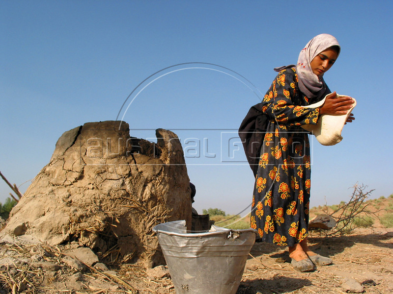 Sabrine Zegum, 14, makes bread for the family in a mud oven outside her home in the countryside south of Baghdad. Her brother Sari, visibly weak and suffering from aches and rashes throughout his body, was infected with HIV when he got contaminated blood two years ago at a hospital where his parents took him with a severe case diarrhea.  <br /> His case highlights the nature of the disease and the health care system. Lacking many medicines after 12 years of economic sanctions, the health system was left with no option but to give him blood to bring him back. Some even speculate about the origin of the blood itself, said to come from a French company.(Australfoto/Douglas Engle)