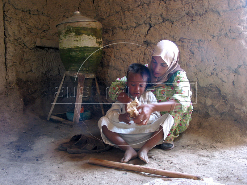 Fatin Hamid Daud, 38, helps her son Sari Zegum, 10, eat in their home in the countryside south of Baghdad. His family does not have much money, but with plentiful crops and livestock, he leads a rich life with his seven brothers and sisters. His downfall came when his parents sought out the modern world to cure a third world disease.<br /> Sari, visibly weak and suffering from aches and rashes throughout his body, was infected with HIV when he got contaminated blood two years ago at a hospital where his parents took him with a severe case diarrhea.  <br /> His case highlights the nature of the disease and the health care system. Lacking many medicines after 12 years of economic sanctions, the health system was left with no option but to give him blood to bring him back. Some even speculate about the origin of the blood itself, said to come from a French company.(Australfoto/Douglas Engle)