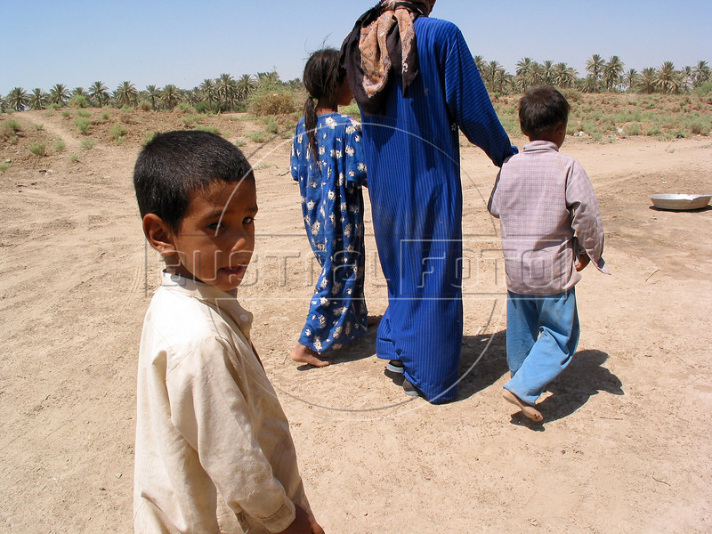 Sari Zegum, 10, right, walks with his mother Fatin Hamid Daud, 38, near his home in the countryside south of Baghdad. His family does not have much money, but with plentiful crops and livestock, he leads a rich life with his seven brothers and sisters. His downfall came when his parents sought out the modern world to cure a third world disease.<br /> Sari, visibly weak and suffering from aches and rashes throughout his body, was infected with HIV when he got contaminated blood two years ago at a hospital where his parents took him with a severe case diarrhea.  <br /> His case highlights the nature of the disease and the health care system. Lacking many medicines after 12 years of economic sanctions, the health system was left with no option but to give him blood to bring him back. Some even speculate about the origin of the blood itself, said to come from a French company. (Australfoto/Douglas Engle)