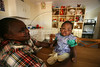 """Mum"" agnes holds 5 month old Caroline in one of the home-style residences at the Nyumbani Children's Home in Nairobi, Kenya, Nov. 26, 2005. Founded in 1992, children live in family style homes, each with its own ""mum,"" a dedicated foster parent. Caroline was abandonded at a hospital by an HIV positive mother, and is still in the probationary period at the home. Because infants carry many of their mothers' antibodies through their first year of life, a number of newborns with infected mothers may give a 'false positive' and never actually develop the disease themselves. In fact, a full 75% of babies who test positive at birth will eventually be found not to have the virus. At Nyumbani, 'home' in Swahili, children are cared for until a definite assessment of their HIV status can be made. Children who are eventually found not to have the virus are adopted or find other homes. Children who are found to be HIV+ are given the best nutritional, medical, in particular, anti-retroviral therapy, psychological, academic, spiritual care available and live at Nyumbani until they become self-reliant. Approximately 100 children from newborn to twenty-three years live at the home.(Australfoto/Douglas Engle)"