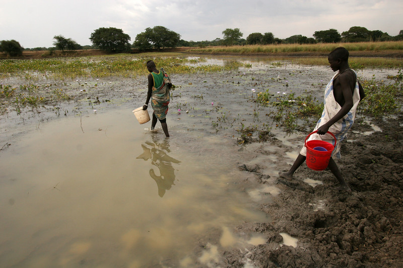 Women wade through standing water to fill their buckets near Rumbek in southern Sudan, Nov. 21, 2005. Many water-related health issues are present in the region, including the deadly Guinea worm, hepatitis and dysentery. Although the peace accord signed in Jan. 2005 ended the war between the Islamic north and non-Muslim south, years of civil war have taken their toll. The presence of any government or infrastructure is minimal, if at all. The missions and other NGOs in the region provide vital basic services for the population, which is slowly growing around the relief and aid centers. While the war is over, the Catholic church sees that the battle with the Islamic Sudanese government for the hearts and minds of the people of south Sudan is just beginning. After a six-year transitionary period, the south Sudanese will vote in a referendum on independence.(Douglas Engle/Australfoto)