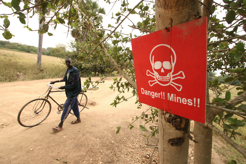 A man walks past a sign warning of landmines near a highway in southern Sudan, Nov. 21, 2005. According to UNICEF, Sudan is one of the ten most landmine-affected countries in the world. Nobody knows precisely how many mines there are in the country, but SudanÕs 21-year civil war has resulted in a tremendously widespread problem with mines and unexploded ordnance.  Since the Jan. 2005 peace accord, hundreds of Sudanese are returning home and may travel through areas that may be rife with landmines or unexploded ordnance. An estimated 15,000 to 20,000 people are killed or maimed by landmines every year, according to the International Campaign to Ban Landmines. (Douglas Engle/Australfoto)