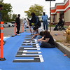 """Volunteers help paint wider curbs and colorful crosswalks on North Clinton Avenue Sept. 29, 2019, during the Complete Streets Makeover. The makeover featured an international flair. Here volunteers are painting the words """"Little San Juan,"""" as the neighborhood has come to call itself, due to a large population of residents who are originally from Puerto Rico."""