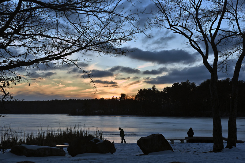 Young couple on the desserted beach at Chelmsford's Heart Pond as the Sun sets in the background. SUN/ David H. Brow