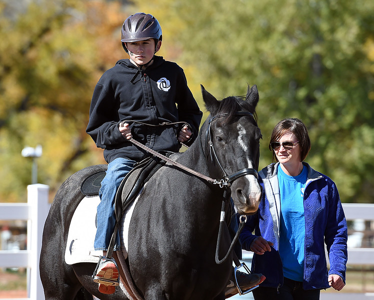 Bill Reed Middle School seventh-grader Nick Chapman, 12, rides a horse named Drifter with Cassie Moxley at their side Tuesday, Oct. 10, 2017, as he they make their way through an obstacle course he set up at Hearts & Horses Theraputic Riding Center in Loveland. Students from five middle schools are spending Tuesdays at the ranch for eight weeks in the Changing Leads program, learning social and emotional skills while working with the horses. (Photo by Jenny Sparks/Loveland Reporter-Herald)