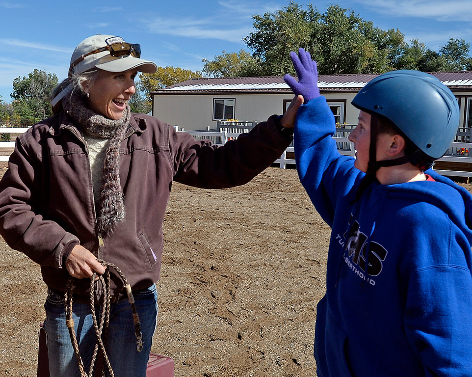 Koda Sterling, 14, a Turner Middle School eighth-grader, right, gets a high-five from Tamara Merritt, left, associate executive director at Hearts & Horses Theraputic Riding Center, for the obstacle course he set up Tuesday, Oct. 10, 2017, tthe ranch in Loveland. Students from five middle schools are spending Tuesdays at the ranch for eight weeks in the Changing Leads program, learning social and emotional skills while working with the horses. (Photo by Jenny Sparks/Loveland Reporter-Herald)