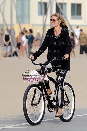 Heidi Klum,Martin Kristen and kids biking on the shore.