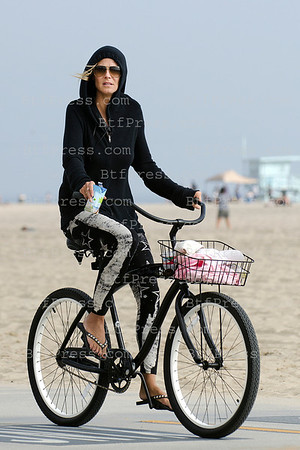 Heidi Klum,Martin Kristen and kids biking on the shore.