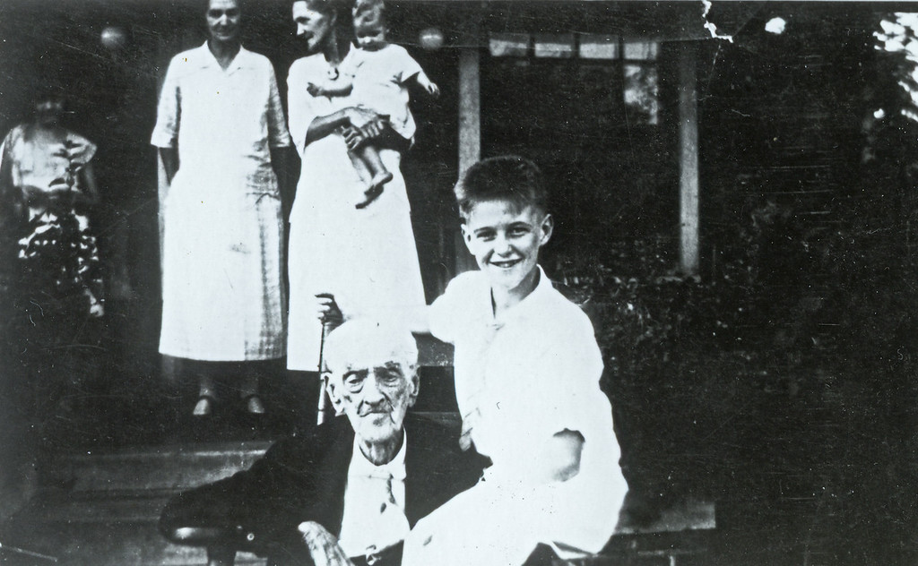 William Lewis Pledger (1860-1917) married Lillie Farrar Pledger (1860-1945), seen on porch holding child.  They lived in Helena, Shelby County, AL.  The boy sitting with him is unidentified.