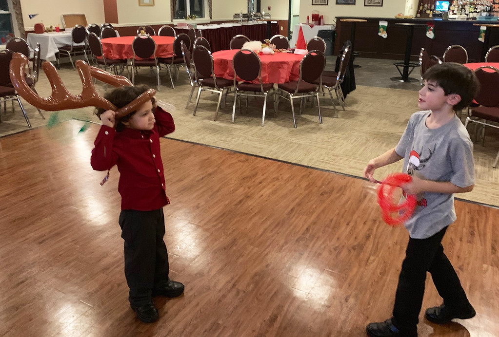 . Liam Harrington of Chelmsford and Will Regan of Ashby play Rudolph ring toss.