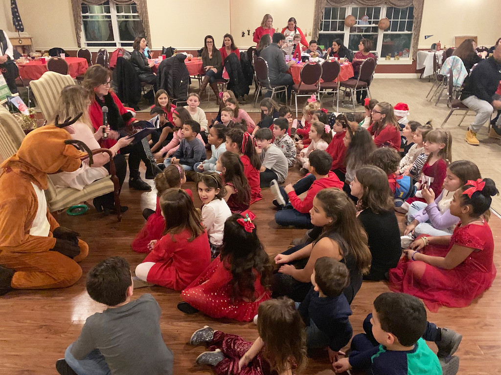 . Co-Principals Pam Murphy and Donna Cullen read �Rudolph, the Red-Nosed Reindeer� to the children, as Rudolph himself listens.