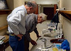 DAVID LACHANCE — BENNINGTON BANNER<br /> John Resio, left, assists George Glanzberg with examinations. The two have worked together for 35 years. Help-A-Pet sets up shop in a hallway at the First Baptist Church once a month.
