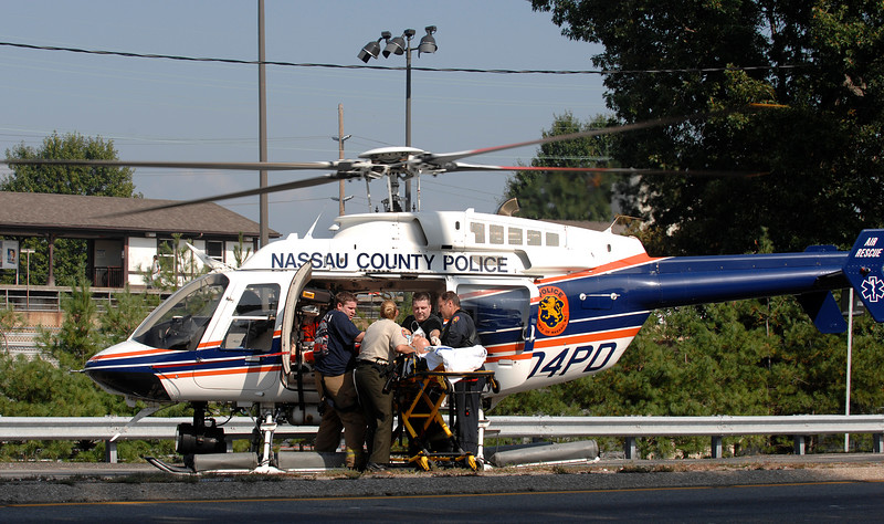 Male accident victim, from Nissan Maxxima, is transported from the ambulancey VS Firemen and NCPD,  at the scene to the waiting NC Police helicopter which landed on Sunrise Highway.  The  Helicopter is on its way to the hospital. Sunrise Highway was closed, in both directions, for over two hours. September 4th, shortly before 2 pm. Photo by Kathy Leistner