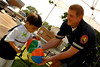 L-R Carlos Mejia, 3, receives key chains and a helping hand from POPs PO Frank D'Andrea, 4th Precinct.  5th Annual Family Unit Day, August 11th, 2007. Photo by Kathy Leistner
