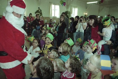Santa Claus (Jose Quezada of Eureka) is greeted by children at the annual Humboldt Child Care Council Christmas party Dec. 12, 1997.  Quezada was Santa Claus at the HCCC parties for a number of years. (Times-Standard file photo)