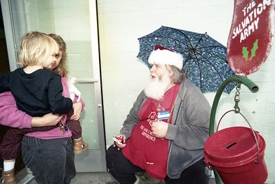 Singing Salvation Army Santa Tom McCauley gives a blessing card to Sara Rae Anderson, 2, of Eureka and her mother, Gidget, outside of the main post office in Eureka on Dec. 11, 1996 (Times-Standard file photo)