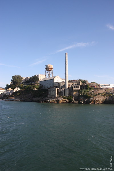 Alcatraz - Power House (foreground) and Quartermaster Warehouse (three-story building immediate left)  Like more than two-thirds of Alcatraz, the power house area was off-limit to prisoners. This did not stop Frank Morris and the Anglin brothers from passing through it in 1962 as they crept down the slick sides of the Rock and began a probably ill-fated swim to freedom. The preparations for the break had been elaborate: they had fashioned tools out of spoons and fans, molded plaster heads to fool the guards into thinking that they were still in their cells sleeping, and built a life raft out of raincoats. On this flimsy craft they wagered their lives. Though the only trace of them ever found was a wallet belonging to Clarence Anglin washed up on nearby Angel Island, many prefer to believe that they made it. The names of Morris and the Anglins live on in Alcatraz folklore, replacing the names of Cole and Roe in many anecdotes and sighting reports.