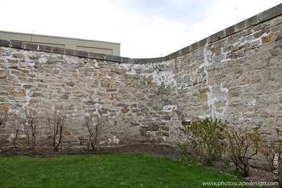 "Yard within walled-in area of the Women's Ward  Before its construction, women did not have separate quarters.  In 1905, inmates built the stone wall around the old Warden's residence.  In 1920,  Warden William Cuddy replaced the two old women's cell buildings with this ""thoroughly modern dormitory.""  This building features a concrete floor and roof, seven two-person cells, one bathroom, a kitchen, and a central day room, which was furnished with comfortable chairs, rugs, and a phonograph.  The walls and barred doors were painted white.    Each cell - designed for two women in bunk beds - had a toilet, electric lights, windows, and a steel bar door.  Steam heat came from the prison's central plant.  The cells are so small that the two occupants had to take turns dressing and undressing.  During the 1920s, a total of 17 women entered the prison.  Their terms ranged from 37 days to over 20 years.  Murderers Lyda Southard and Mary Crumroy spent 15 and 21 years here respectively."