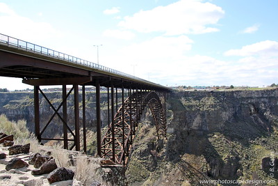 Perrine Bridge - Twin Falls  The I. B. Perrine Bridge at Twin Falls, Idaho, United States is a truss arch four-lane bridge carrying U.S. Highway 93 over the Snake River Canyon. Perrine Bridge is approximately 1,500 feet (457 m) long and 486 feet (148 m) above the Snake River. This beautiful 1500-foot span runs north and southbound on Route 93 and is the main connector between Twin Falls County and Jerome County.  Originally named the Twin Falls-Jerome Intercounty Bridge, a steel cantilever bridge was opened to traffic in September 1927, and at the time, was the highest bridge in the world. The privately financed $650,000 structure was originally a toll bridge, but the tolls were eliminated in 1940 after the bridge was purchased by the state of Idaho.  By the early 1970s, the original bridge was outdated and unable to handle heavy loads and required replacement. Construction on the current bridge was completed in July, 1976 at a cost of $9,700,000. The original bridge was demolished.  The bridge is named for I. B. Perrine, who spearheaded the early 20th Century irrigation projects in Idaho's Magic Valley region and is largely credited as the main founder of Twin Falls.  Perrine Bridge is the only man-made structure in the United States where BASE jumping is allowed year-round without a permit.