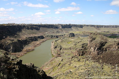 Snake River Canyon - Twin Falls  Snake River Canyon is a large canyon formed by the Snake River in the Magic Valley region of southern Idaho.   Perrine Bridge crosses the canyon immediately north of Twin Falls. In places, the canyon is 500 feet (166 meters) deep and 0.25 miles (0.41 kilometers) wide. Shoshone Falls is located approximately 5 miles (8.33 kilometers) east of Perrine Bridge in the canyon. [That's our next stop on this journey.]  The Snake River is a major river of the greater Pacific Northwest in the United States. At 1,078 miles (1,735 km) long, it is the largest tributary of the Columbia River, the largest North American river that empties into the Pacific Ocean.  The Snake has been called the lifeline of southern Idaho and the multi-billion-dollar agricultural industry in that part of the state. Hydropower dams and irrigation facilities were developed simultaneously along the Snake, as pumping facilities were powered by electricity and communities developed around the farm settlements.  The  Snake River Plain is a geologic feature located primarily within the state of Idaho. It stretches about 400 miles (640 km) westward from northwest of the State of Wyoming to the Idaho-Oregon border. The plain is a wide flat bow-shaped depression and covers about a quarter of Idaho. Three major buttes dot the plain east of Arco, Idaho, the largest being Big Southern Butte - one of the largest volcanic domes on earth.  The Snake River Plain can be divided into three sections: western, central, and eastern. The western Snake River Plain (this photo is part of the western section) is a large tectonic graben or rift valley filled with several km of lacustrine (lake) sediments; the sediments are underlain by rhyolite and basalt, and overlain by basalt.  Many of Idaho's major cities are in the Snake River Plain, as is much of its agricultural land. Also located within Snake River Plain is the Idaho National Laboratory.