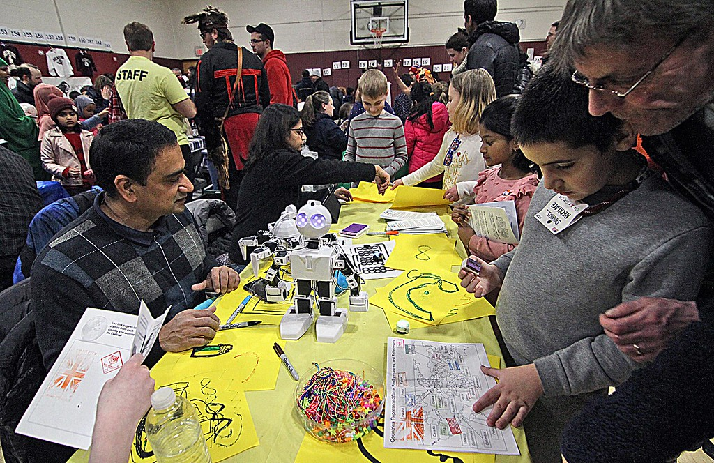 """. Getting an India stamp in his \""""passport\"""" at the Heritage Festival at Harrington School is Cameron Lussier, 8, with his grandfather, Michael Baker, on right. On left is vendor Arvind Jagannath with the Adventure Code Academy of Chelmsford. SUN/ David H. Brow"""