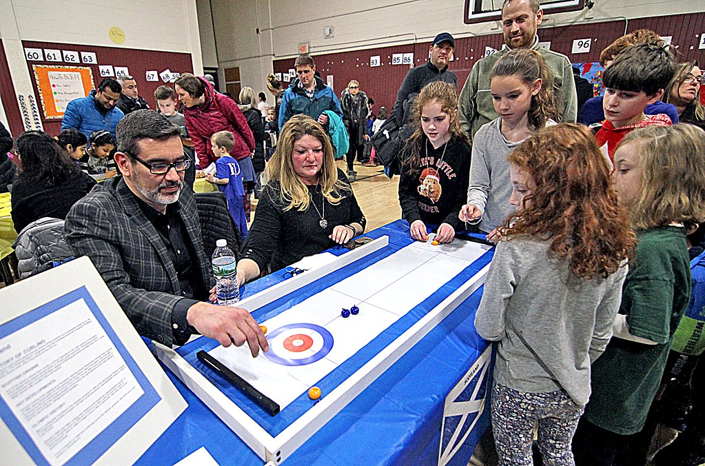 . Students try their luck at tabletop curling at the Scotland table manned by Jim and Jill Cairns at the Harrington School Heritage Festival. SUN/ David H. Brow