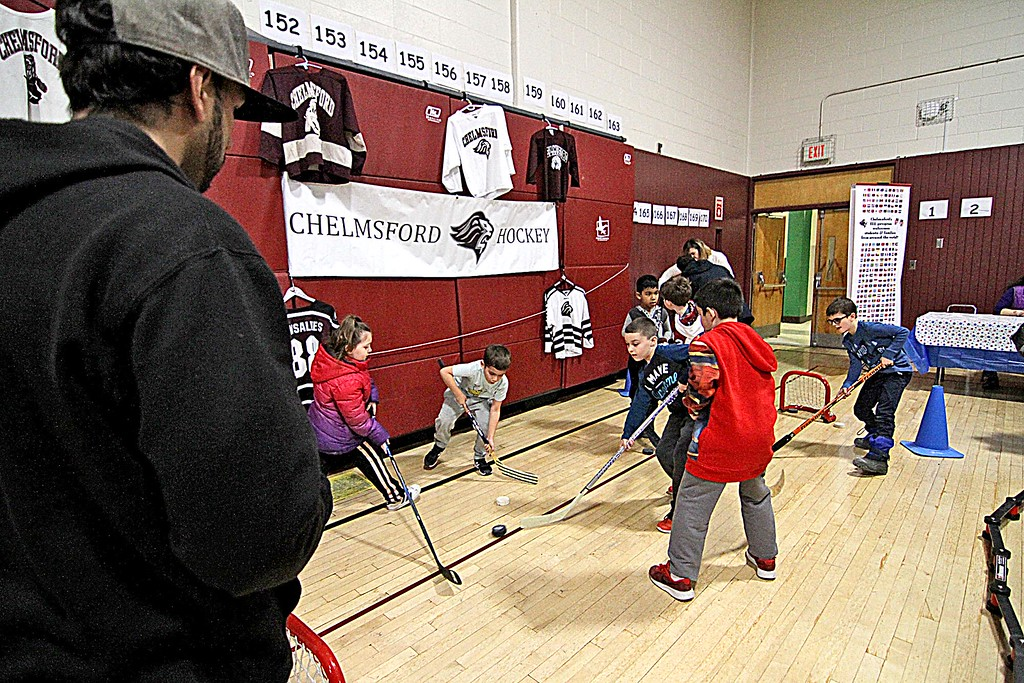 . Students try their hand at stick hockey with the Chelmsford Hockey Association at the Harrington School Heritage Festival. SUN/ David H. Brow
