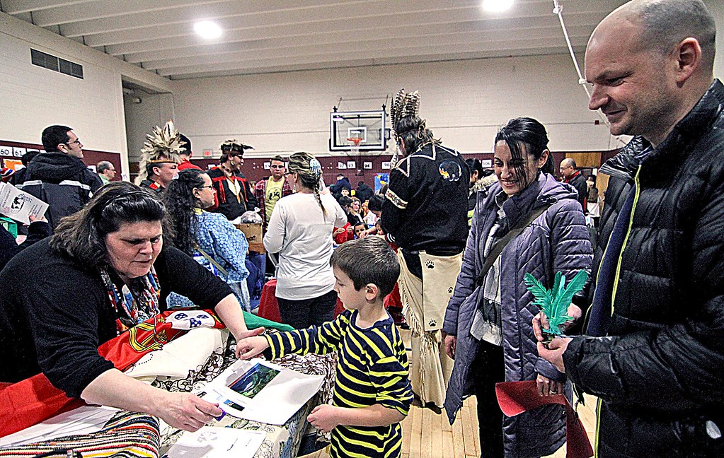 """. Maria Santos, left, puts the stamp of Portugal on the \""""passport\"""" of Lucas Conde, 6, at the Heritage Festival at Harrington Elementary School. Behind Lucas are his parents, Becky Conde and Chris Conde, whose parents are from Graciosa, Azores, Portugal. SUN/ David H. Brow"""