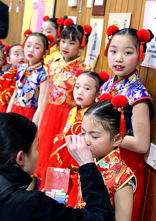 . A dance instructor puts on last touches of makeup to one of the dancers from the Chelmsford Chinese Language School at the Harrington School Heritage Festival. SUN/ David H. Brow