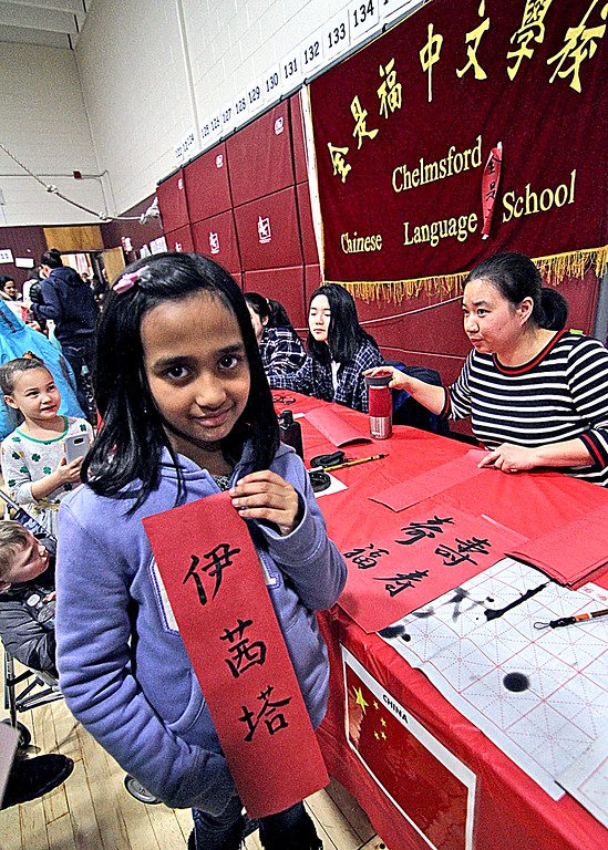 . Harrington School third grader Ishita Pharande, 8, shows her name just written in Chinese by Yuexian Huang, a second grade teacher at the Chelmsford Chinese Language School. SUN/ David H. Brow