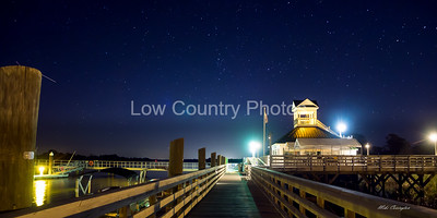 Night scene of the Heritage Plantation marina clubhouse and pier with stars and moon showing in the sky