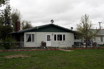 Bill and Hallie's original home is contained within the expanded and remodeled home of Lew and Helen Janssen.   The wind generator tower is to the left; the bunk house to the right.