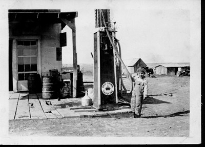 Circa 1929   John M. Janssen, son of Bill & Hallie, out front of the Mercantile, tugging on the hose of a Red Crown Gas pump  The buildings seen in the background (north) belonged to Fred & Lois Janssen. Bill & Hallie's home and out buildings would have been further east (right).