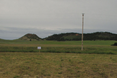 (Looking south from where John and Anna's frame house stood. That's Twin Buttes on the horizon, left.)    The stake indicates where the second post office and store stood, just north of the east-west road (hidden from view by grass).