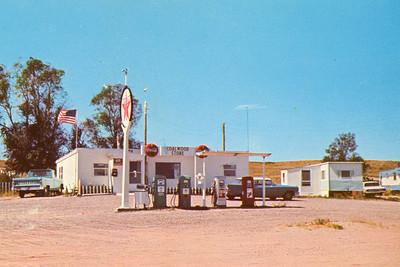 Postcard Image Circa 1960   A new cement block structure replaced the wood-frame building. The post office occupied the southeast (near left) corner. Living quarters, a lunch counter, small grocery store, fuel pumps, and restroom comprised the rest of the operation.  The Seeleys sold the enterprise to Dan and Dielda Bartholomay in 1957. Dielda passed away in July 1964, at which time Dan sold the store and post office to John and Margaret Gunther. Margaret took over the duties of Clerk in Charge. To maintain mail service in the interim, Lewis Janssen stepped in as acting clerk. Lew was the grandson of John W. Janssen (1912 postmaster) and the son of William M. Janssen (1920 postmaster).  The last postmark stamped at Coalwood, Montana, was dated April 31, 1973. The post office officially ceased operation on May 1, 1973. Those with former Coalwood addresses have since received mail addressed to Volborg, Miles City or Broadus. This building, located just off Montana Highway 59, is now a private residence.  The Coalwood School was located to the northwest (right).   ------------  From the reverse: The Friendly Stop on Hiway #312 COALWOOD STORE Owned and operated by John & Margaret Gunther Gas, Diesel, Oil, Batteries, Tires, Trailer Stalls  ------------  Coalwood, Montana Postmasters/Clerks: John W. Janssen commissioned: July 9, 1912 William M. Janssen: March 17, 1920 Zelma Edmondson: Jan. 31, 1935 Horace Browne: Nov. 9, 1939 Gene Severovic, Clerk in Charge: May 31, 1956 Josie Mae Seeley: May 7, 1957 Dielda Bartholomay: June 7, 1957 (Bartholomay deceased July 16, 1964, at which time Coalwood became a Rural Station of Miles City) Lewis Janssen: Acting Clerk until official appointment of ... Margaret Gunther, Clerk in Charge: 1964 Closed: May 1, 1973
