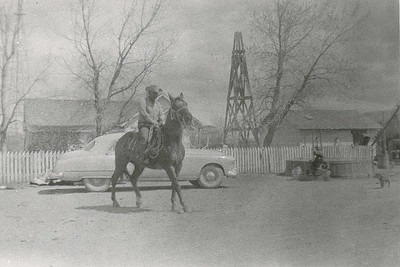 John Janssen horseback in front of Janssen home at Coalwood  Circa 1952   The tower at the far left of the photo is a wind generator, used to produce electricity. The wooden tower to the right, missing the blade and motor assembly, is a windmill formerly used to pump water. Round tank with pumpjack provided water after the windmill.  The building to the far right, with an angled grain auger, is a granary. It would later become the bunk house.