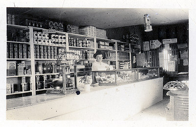 """Shopkeeper and Postmaster: Circa 1920   Bill behind the counter at Janssen Mercantile (a.k.a. The Coalwood Store)  When he returned from the war, Bill built a house on his homestead and """"went to farming.""""   In 1920, John W. retired from the family business due to poor health. He and Anna moved to Miles City. When John W. regained his health, he once again worked as a carpenter. He and Anna also operated Fair Price Grocery.   Bill bought the Coalwood Store and Post Office and was appointed postmaster. In July of that same year, he married Hallie Warkins. The Warkins family arrived in Montana on Easter Sunday 1913, homesteading a few miles south of Coalwood.   Bill and Hallie lived in a small building that had previously housed the post office. He described it as being 10x10' with rough lumber interior walls. Grandma said it was 8x10'. (In her defense, I suppose it felt smaller. Granddad was a busy kinda guy who found it hard to sit still.) They eventually moved the house from his homestead to Coalwood and added to it as their family grew.   BIll and Hallie ran the store and post office for 14 years, while also raising horses, cattle, four kids and several large gardens. Bill continued to work with horses, noting that he broke a lot in his lifetime, and he was a 4-H leader.   Regarding the mercantile, Bill commented, """"In 1933 and '34, business got pretty slow. A lot of our business was delivering relief food for the government: meat, wheat, etc.""""   In 1934, they traded the store and post office for a section of land on Pumpkin Creek and concentrated on farming and ranching. Of that year's crop, Bill said, """"I raised 1,700 bushels of wheat and sold it for a little over $300, delivered to Miles City."""""""