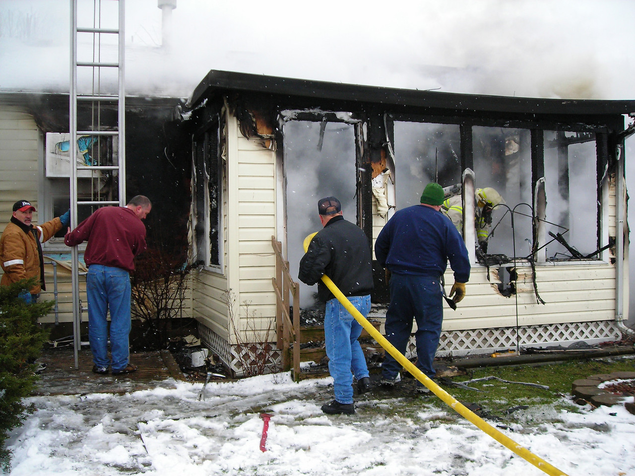 Utility workers and off duty police officers assist firefighters at a residential fire.