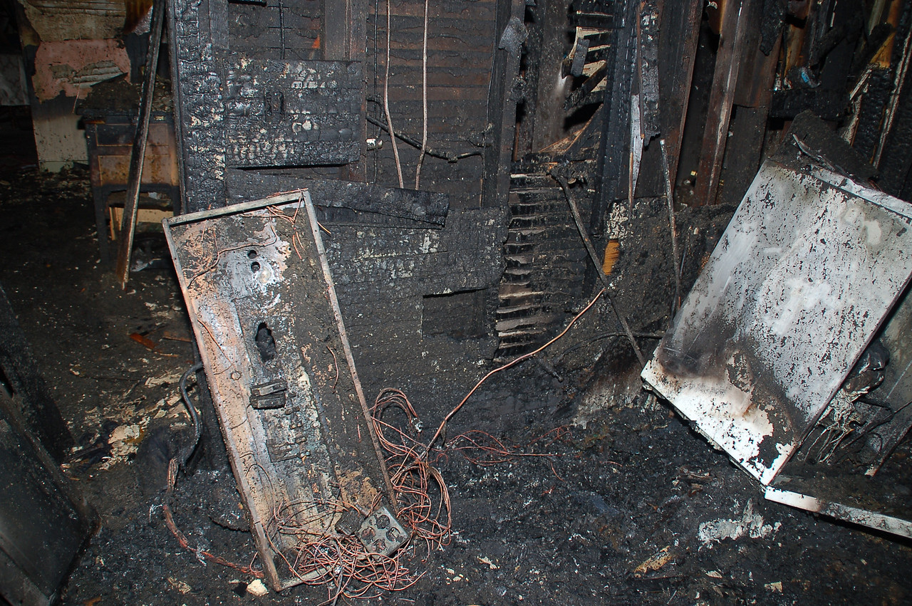 The fire started behind a spare refrigerator in a remodeled room.  The refrigerator was located to the left of the washer (in the right of the photo).   The burn pattern on the wall next to the washer indicates that fire originated near the floor.<br />    The main electrical panel is in the left of the photo.   Note the hole burned through the back of the enclosure.   The intense heat melted the plastic components, resulting in an electrical arc.   This created a second ignition source.