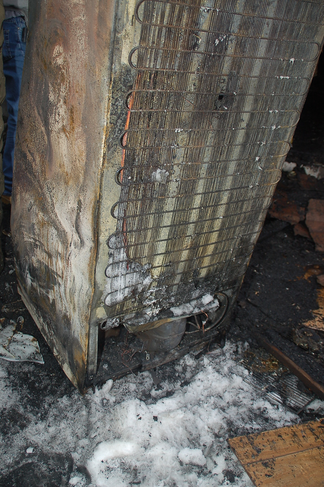Rear view of the refrigerator which caused the fire.  It was taken outside during firefighting operations.