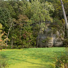 Duckweed-covered, spring-fed pond under a limestone bluff