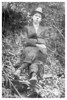 Unknown man sitting on small stool in wooded area
